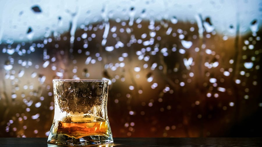 Glass of whiskey with rainy background